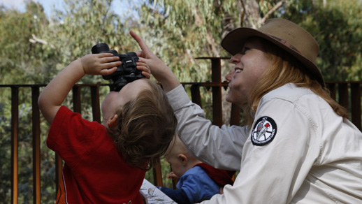 Photo of a ranger and child with binoculars.